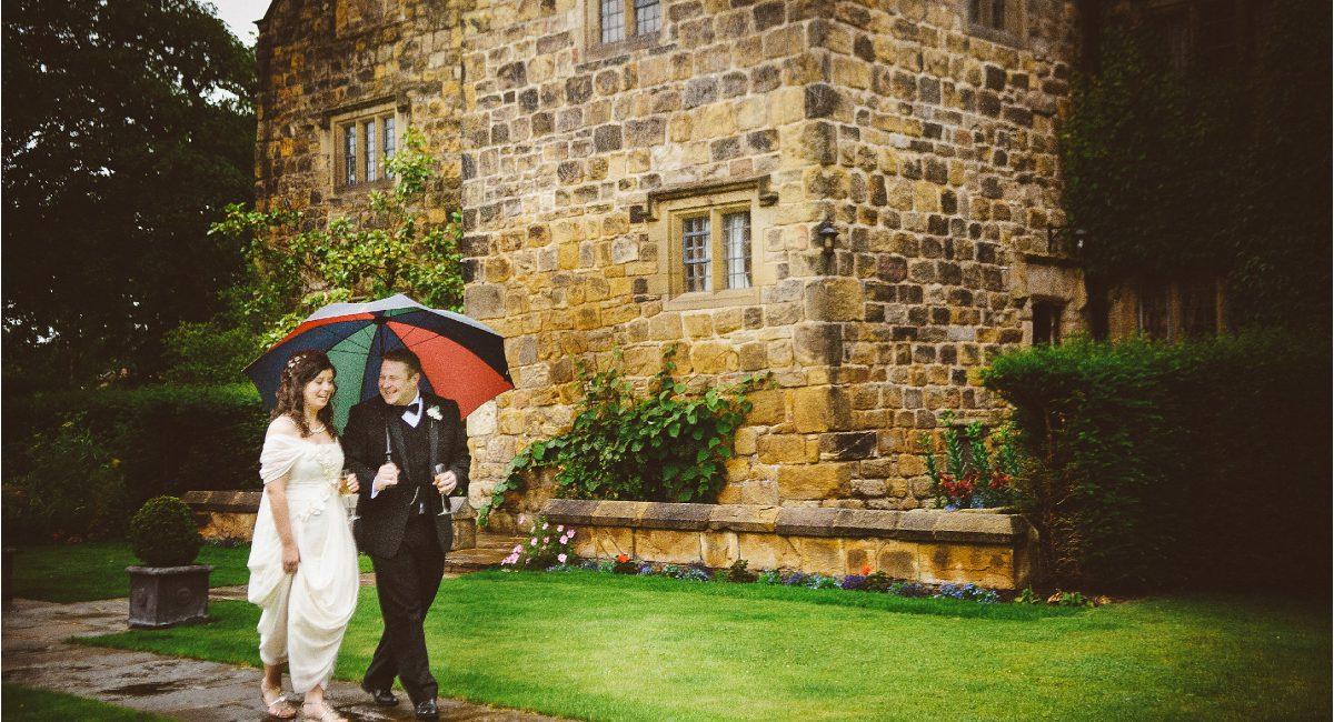 bride and groom under umbrella in the rain