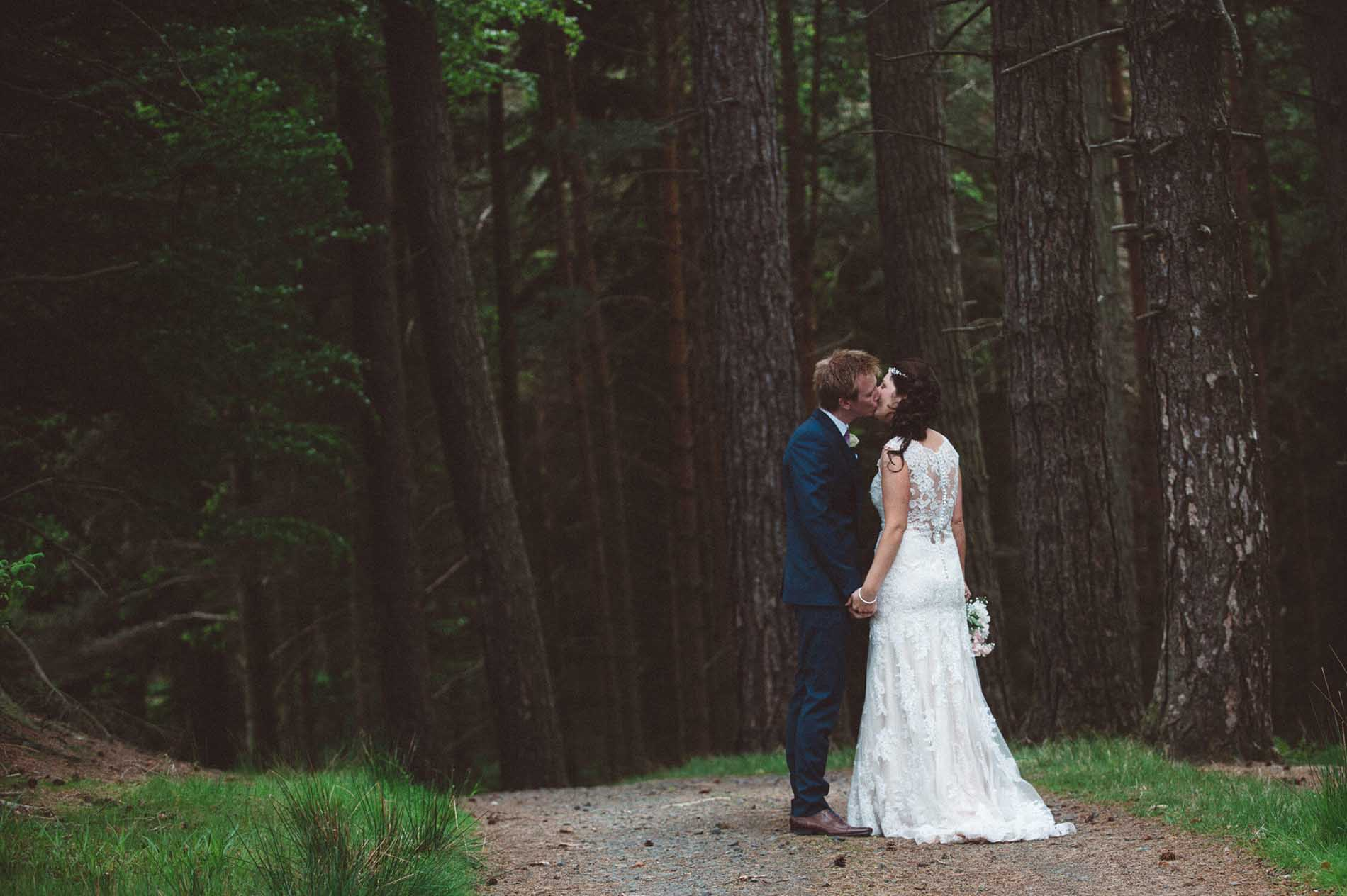 groom kissing his bride in forest near Alnwick