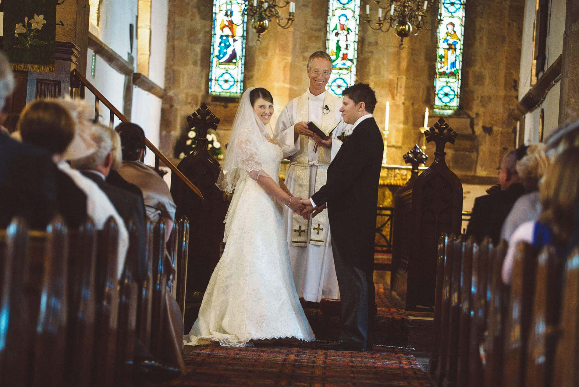 bride smiles at family during ceremony Bywell church tyne valley